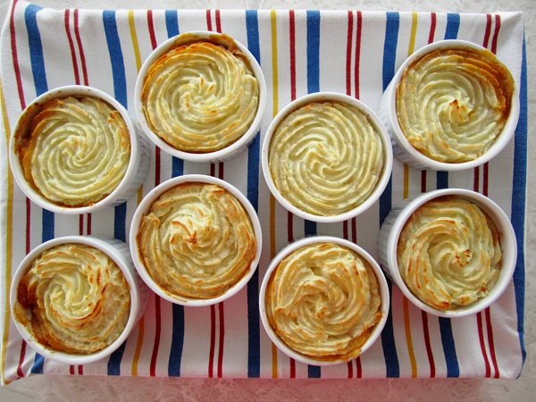 Individual cottage pies / shepherd's pies in ramekins with decorative piped mashed potato topping, on a colorful striped background