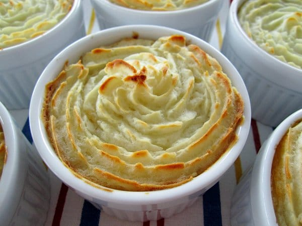 Individual cottage pies / shepherd's pies in ramekins with decorative piped mashed potato topping