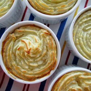 overhead closeup of individual cottage pies in ramekins with decorative piped mashed potato topping