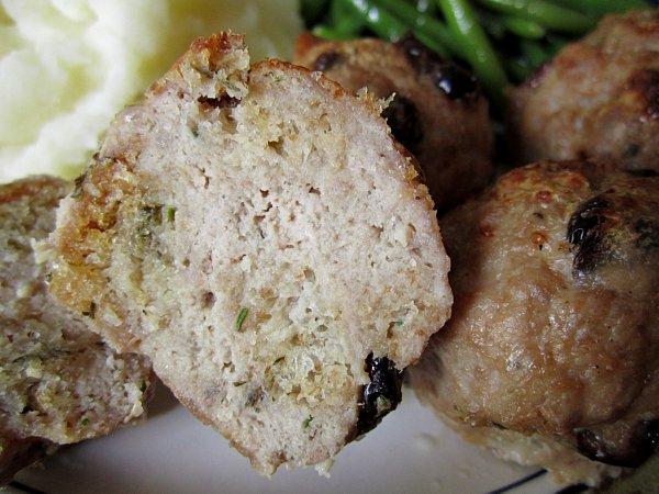 A closeup of a halved meatball on a plate