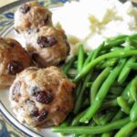 a closeup of meatballs and green beans on a plate