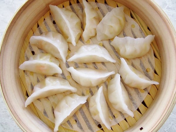 overhead view of white steamed dumplings in a bamboo steamer basket