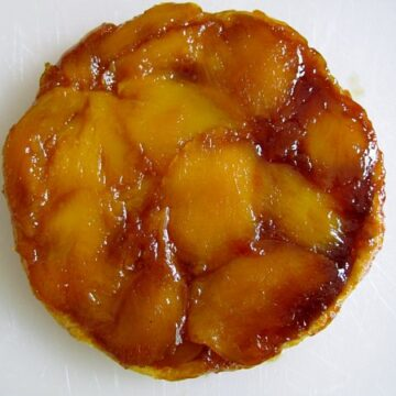 overhead view of a caramelized mango tart on a white surface