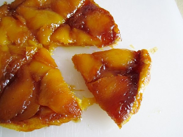 a sliced mango tart on a white surface