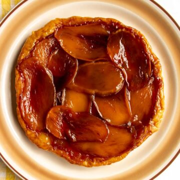 A caramelized layer of sliced mangos on a round tart served on a platter.