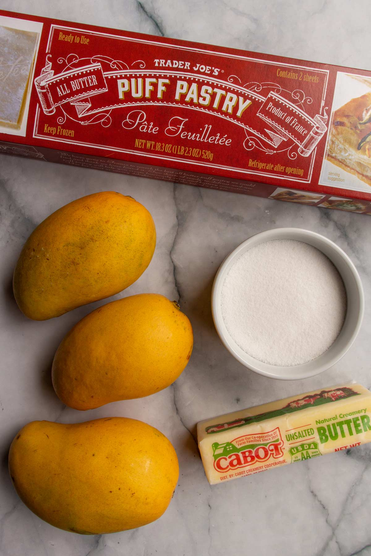 A box of puff pastry, 3 mangos, a ramekin of sugar, and a stick of butter.
