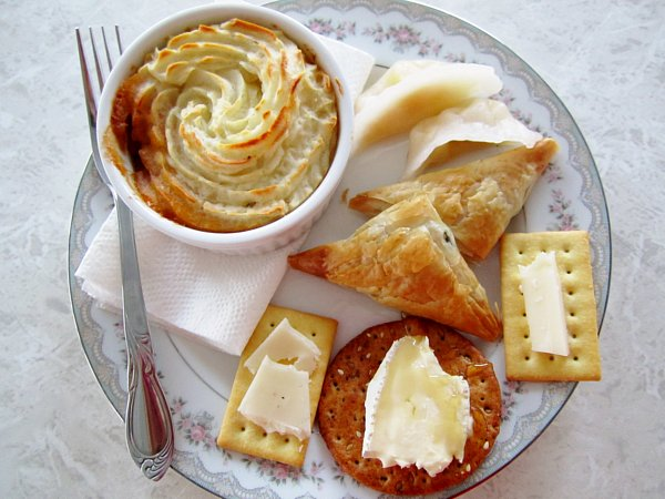 overhead view of a plate of cheese with crackers, dumplings, spanakopita, and an individual cottage pie