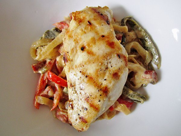 overhead view of a grilled chicken breast over cooked peppers and onions in a white dish