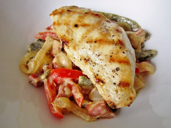 closeup of pollo a las rajas or chicken over peppers and onions on a white plate