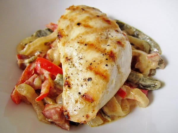 A closeup of a grilled chicken breast over cooked peppers and onions in a white dish