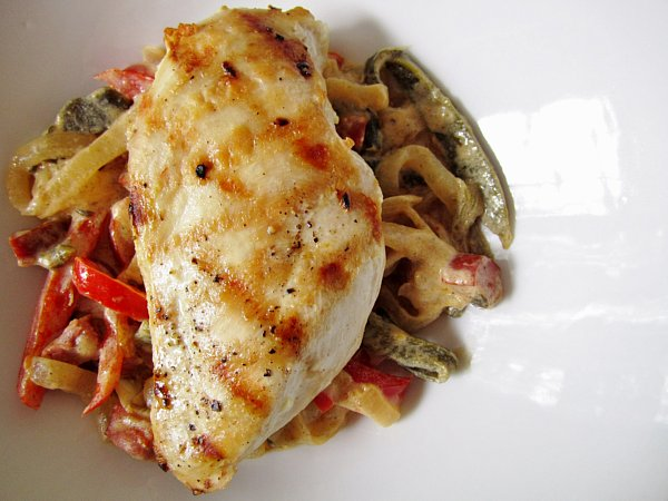 overhead closeup of a grilled chicken breast over cooked peppers and onions in a white dish