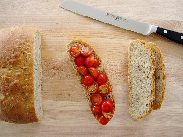 overhead view of sliced bread topped with halved cherry tomatoes on a wooden board
