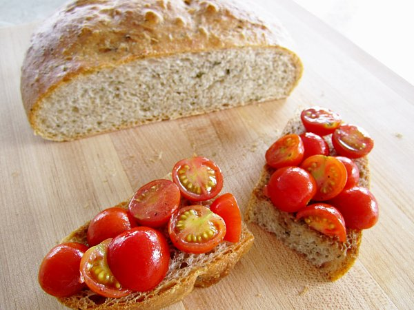 two pieces of bread topped with cherry tomatoes on a wooden board