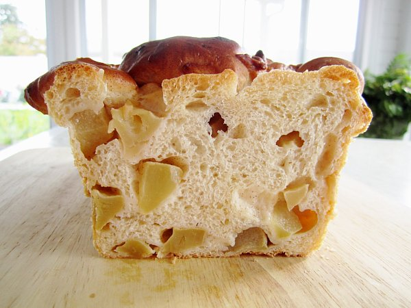 a cross section of an apple cinnamon loaf with cubes of apple inside