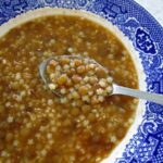 closeup of a bowl of lentil soup with macaroni with a spoon scooping some out