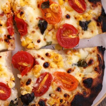 overhead closeup of sliced corn and tomato pizza on a plate
