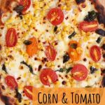 overhead view of a charred and bubbly corn and tomato pizza