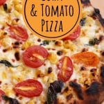 closeup of a bubbly and charred corn and tomato pizza on a wooden board