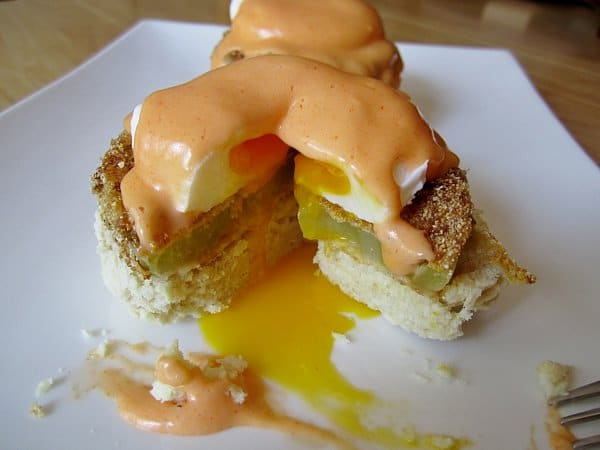 A half eaten eggs Benedict on a plate with buffalo hollandaise sauce and oozing egg yolk