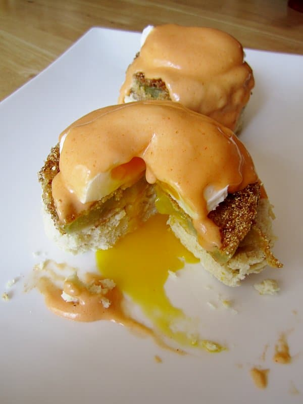 half-eaten fried green tomato Benedict with Buffalo Hollandaise sauce on a white plate