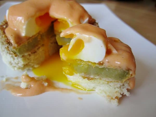 A closeup of a bite of Eggs Benedict on a biscuit with fried green tomato