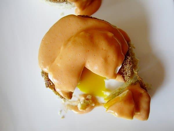overhead closeup of a half-eaten Eggs Benedict topped with Buffalo Hollandaise sauce