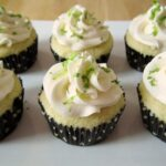 six white cupcakes with white frosting and lime zest garnish on a white plate