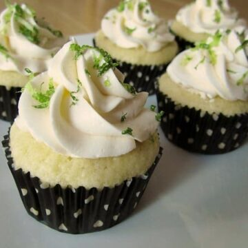 a closeup of margarita cupcakes in black and white polka dot liners on a white platter