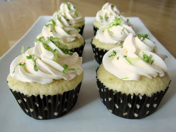 a white platter topped with margarita cupcakes with black polka dot wrappers and lime zest garnish