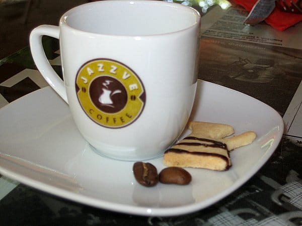 A coffee cup on a table with a small cookie and coffee beans on the side