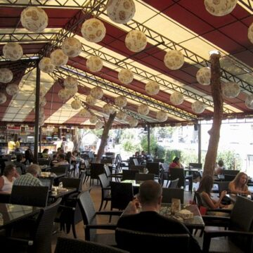 A group of people sitting at an outdoor cafe with a tent and paper lanterns overhead