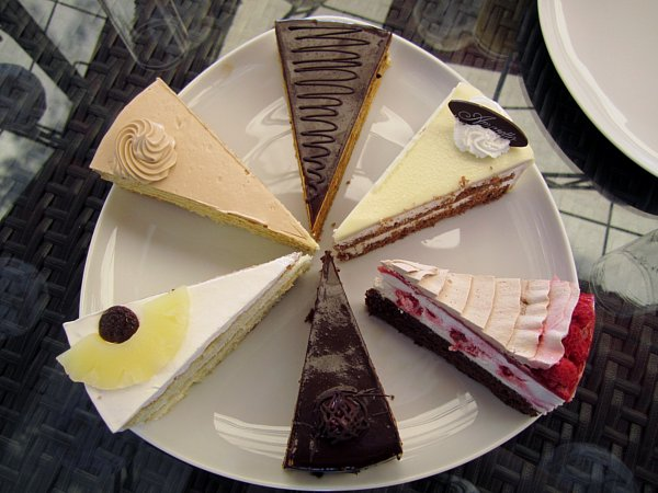overhead view of a white platter of different types of cake slices