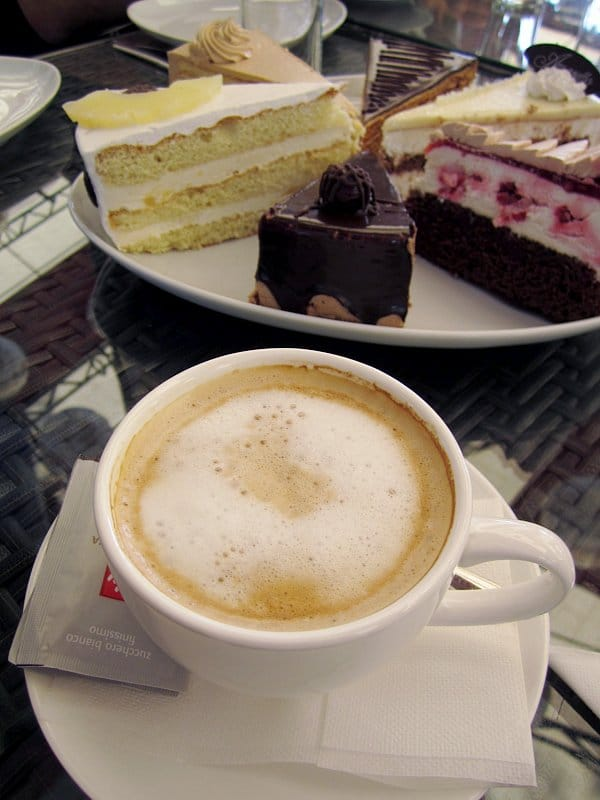 a cappuccino on a table with a platter of cake slices in the background