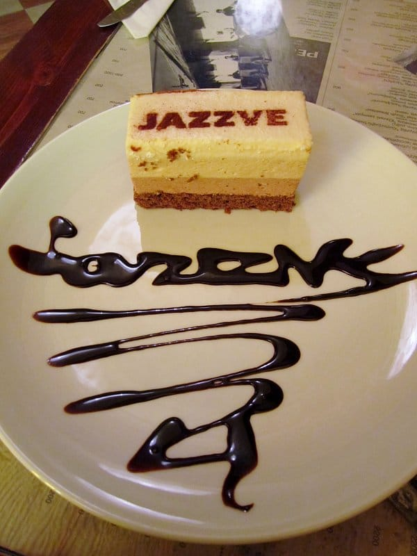 A piece of cake on a plate with Jazzve written on the plate in chocolate syrup