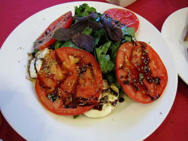 A white plate of salad with tomato and mozzarella slices with balsamic vinegar