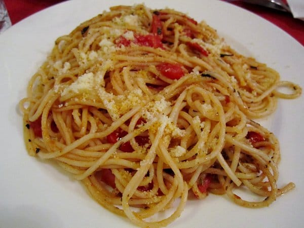 A closeup of a plate of spaghetti with tomatoes and cheese