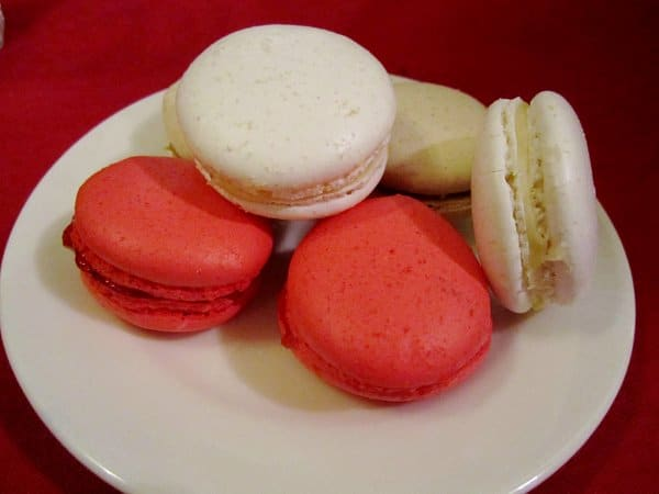 A plate of white and red macaron cookies