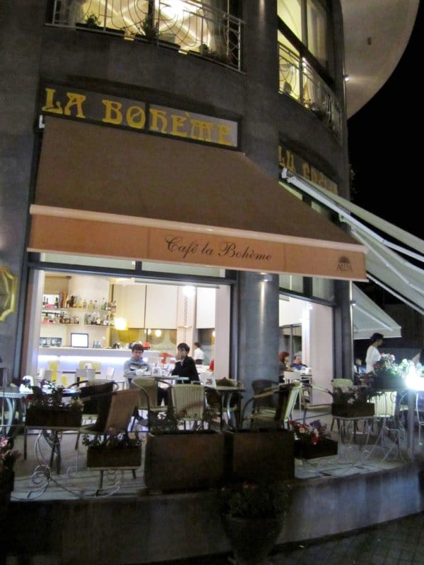 exterior of a restaurant at night with a sign that says La Boheme