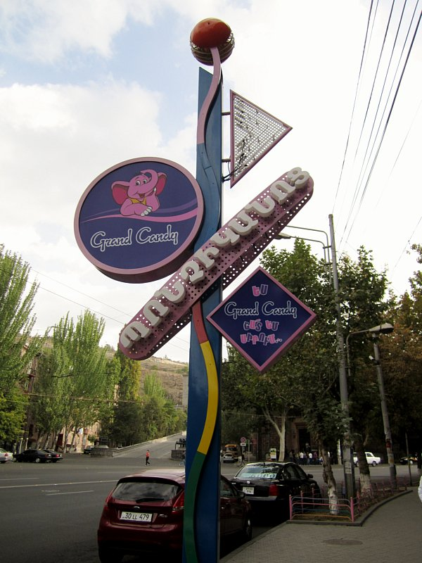 An outdoor sign that says Grand Candy with the image of a pink elephant