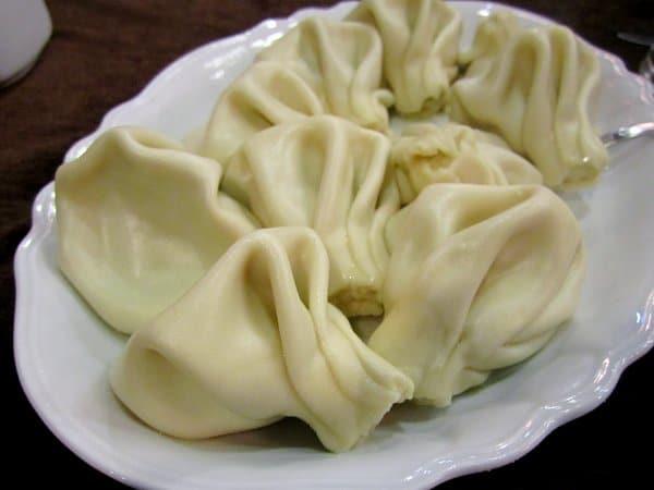 a white platter of large khinkali dumplings