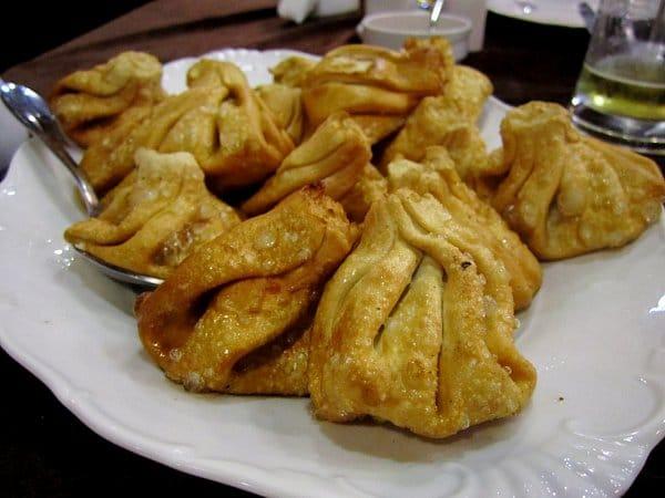 a white platter of deep-fried khinkali dumplings
