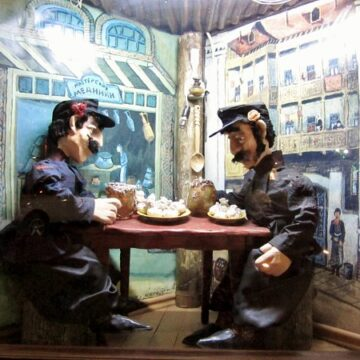 two statues of men sitting at a table and eating food