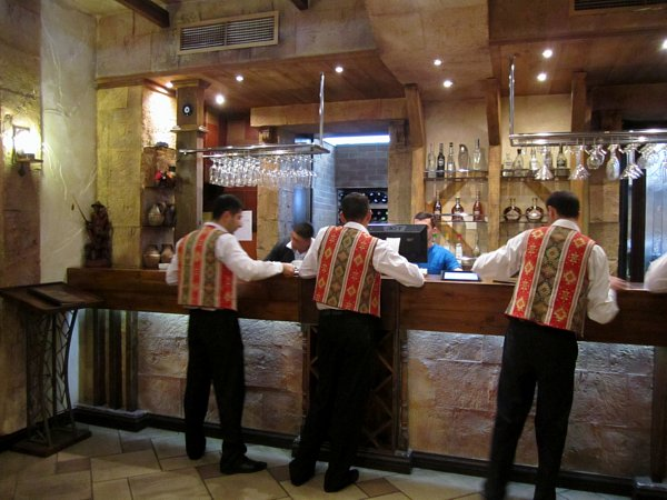 A group of people in uniforms standing in front of a restaurant bar