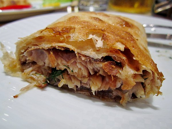 A closeup of a cross section of a fried wrap filled with fish