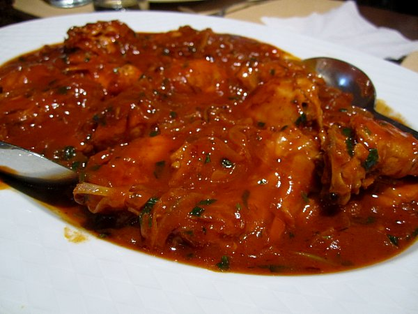 A closeup of a platter of braised meat in a bright red tomato sauce with herbs