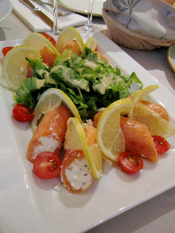 a plate of smoked salmon rolls filled with goat cheese and served with salad and lemons