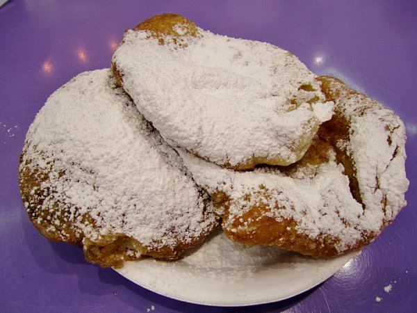 A closeup of white plate topped with ponchik doughnuts covered in powdered sugar