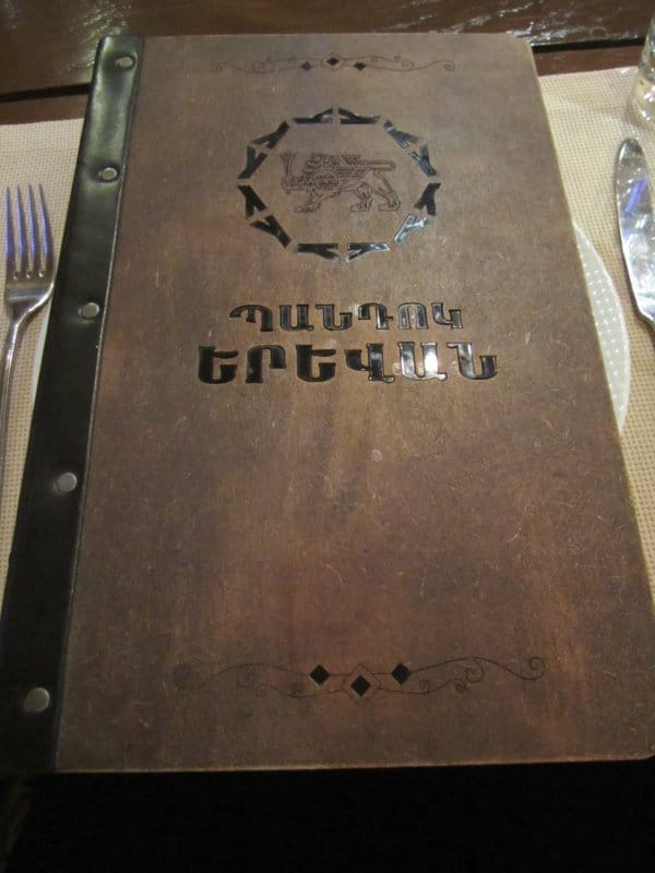 a restaurant menu with a dark brown cover on a table