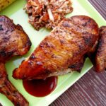 Closeup of smoked bbq chicken on a green plate with slaw and grilled corn.
