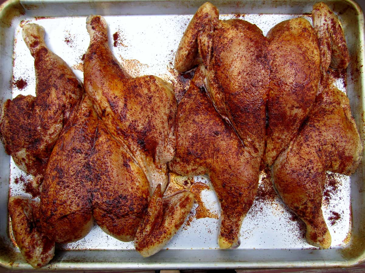 Two spatchcock chickens seasoned with chili powder on a metal baking sheet.